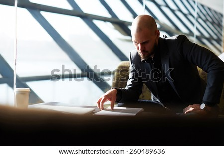 Elegant businessman examining paperwork in bight light office interior sitting next to the window, attractive business man read some documents before meeting, soft focus - stock photo
