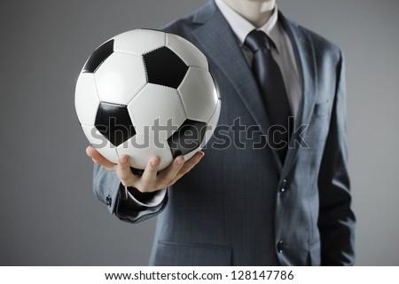 Elegant businessman holding a soccer ball, close up - stock photo