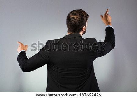 elegant businessman pointing the wall, on grey background