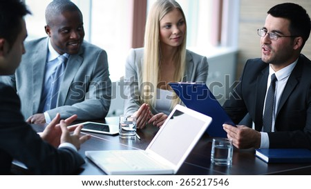 Elegant businessman presenting project to managers at meeting - stock photo