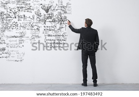 Elegant businessman rear view sketching with a black marker on a white wall. - stock photo