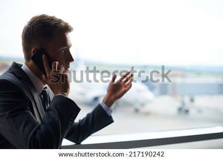 Elegant businessman speaking on cellular phone in airport - stock photo