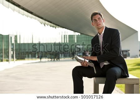 Elegant businessman using hi PC tablet while sitting on a benc outdoors - stock photo