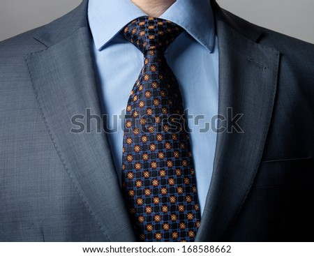 Elegant businessman wearing formal suit and tie, dark background - stock photo