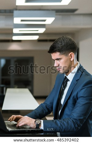 Elegant businessman with the laptop, concentrated on his work