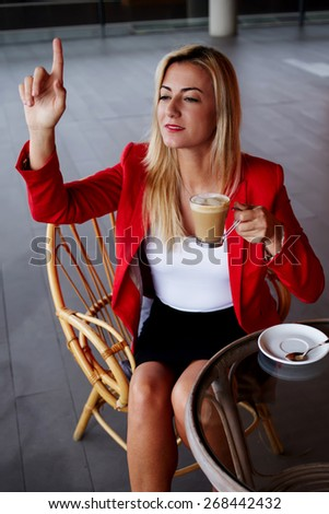 Elegant businesswoman calling for waiter while sitting at coffee shop, business lunch break of female executive, consumer asking for a bill at cafe - stock photo