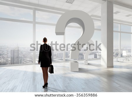 Elegant businesswoman in modern office interior against window panoramic view - stock photo