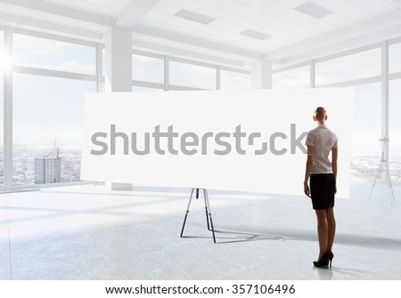 Elegant businesswoman in modern office interior against window panoramic view looking at blank banner - stock photo