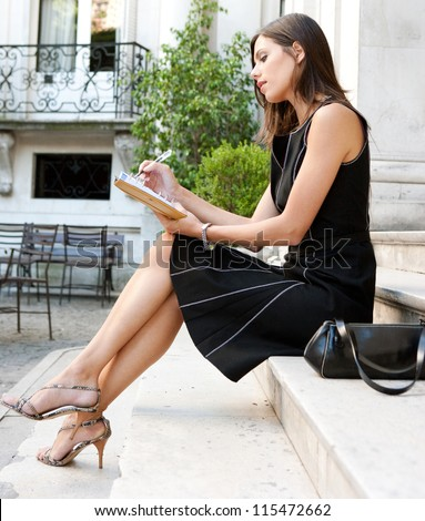 Elegant businesswoman sitting on a classic buildings steps, taking notes in her agenda.