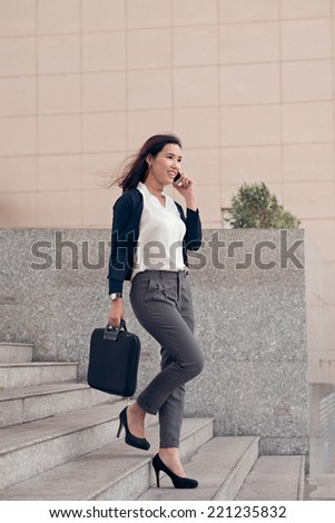 Elegant businesswoman talking on the phone while walking outdoors - stock photo