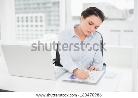 Elegant businesswoman with graphs and laptop in bright office