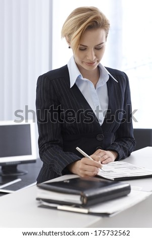 Elegant businesswoman working on business diagrams. - stock photo