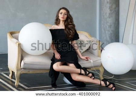 Elegant calm woman in black dress and shoes with long brunette curly hair sitting on sofa in interior in minimalism style and holding white balloons. Vogue fashion style portrait