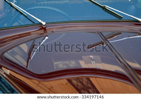 Elegant car macro with shining hood and window wipers.