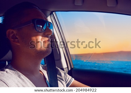 Elegant caucasian male driving car near sea at sunset