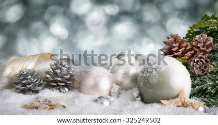 Elegant Christmas arrangement with snow covered silver baubles, nicely curved ribbons and pine cones, with glittering bokeh background