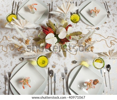 Elegant Christmas or Wedding table with flower arrangement and prawn cocktail - stock photo