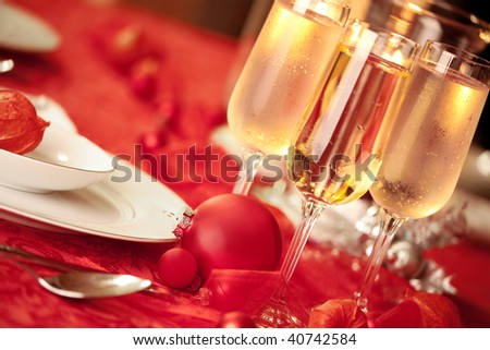 Elegant Christmas table setting in red with a Christmas ornament  as focal point - stock photo
