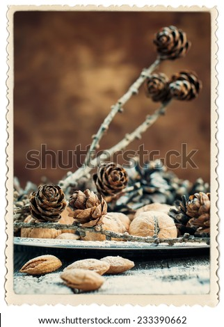 Elegant Christmas Vintage Card with Photo frame isolated on white. Natural Fruits on Silver Tray with Pine cones, Walnuts, Almonds, Nuts on Wooden Background - stock photo