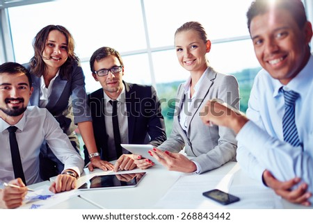 Elegant co-workers looking at camera during meeting in office - stock photo