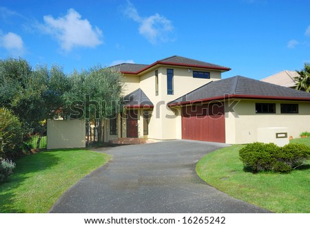 elegant contemporary residential house exterior with blue sky background - stock photo