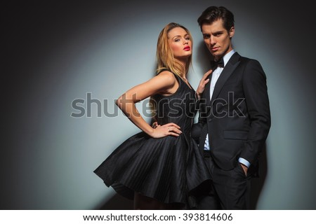 elegant couple in black posing together in studio . the man is looking at the camera with hand in pocket while woman is leaning to him touching his chest while one hand is on her waist.
