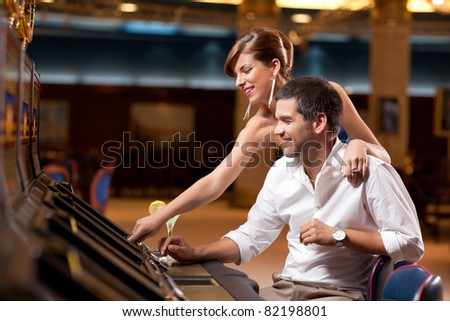 elegant couple playing slot machine in casino - stock photo