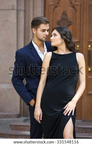 Elegant couple pose outdoors - stock photo