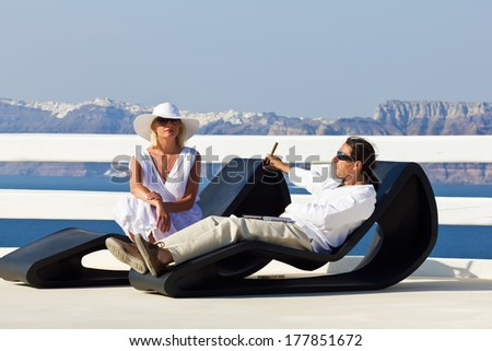 Elegant couple resting at the terrace on Santorini island, Greece