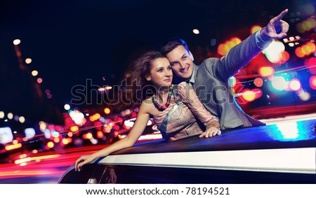 Elegant couple traveling a limousine at night - stock photo