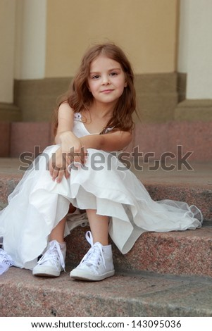 Elegant cute little girl in a white dress with beautiful hair in sneakers