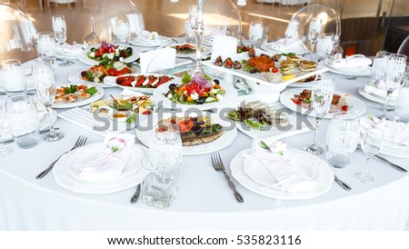 Elegant decorated table with meal and tableware at wedding reception closeup