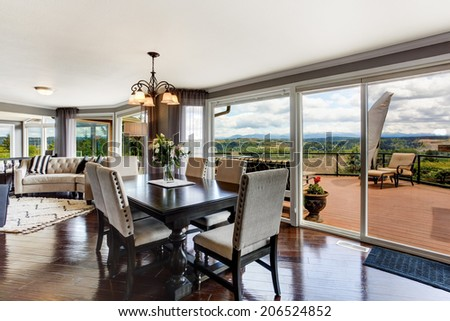 Elegant dining area with walkout deck in luxury house.