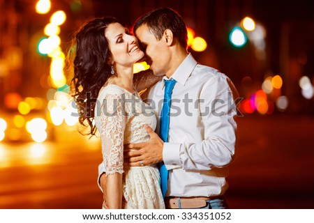 Elegant dresses man is tenderly embracing happy smiling woman at bright night street lights background.