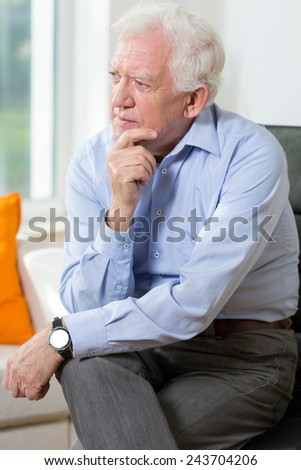 Elegant elderly man sitting on the chair - stock photo