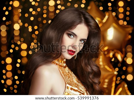 Elegant fashion brunette woman portrait in gold. Wavy hair style. Red lips Makeup. Healthy shiny hairstyle. Sexy girl model in golden dress over bokeh lights background.