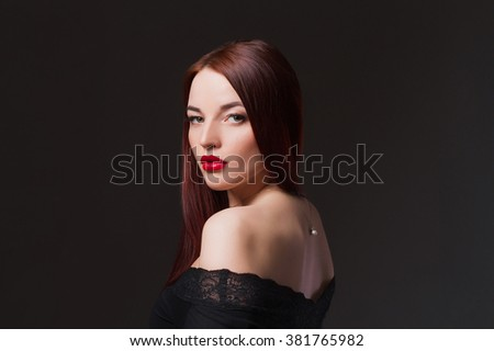 Elegant fashion photo of glamor beautiful young woman in a black sexy dress posing in the studio,luxury.beauty brunette girl - stock photo