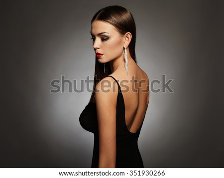 Elegant fashion photo of glamor beautiful young woman in a black sexy dress with open back wearing jewelry and posing in the studio,luxury.beauty brunette girl - stock photo