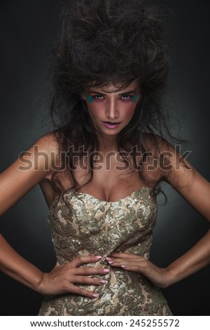 Elegant fashion woman looking at the camera while posing with her hands around her waist. - stock photo