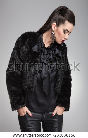 Elegant fashion woman looking down while holding both hands in pockets. - stock photo