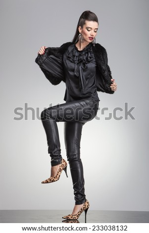 Elegant fashion woman pulling her fur coat while lifting one leg up, looking down.