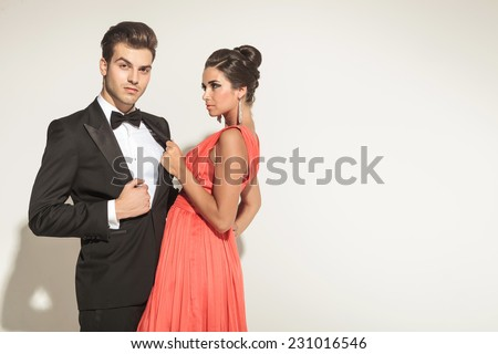Elegant fashion woman pulling her lovers tuxedo while she is looking at him. - stock photo
