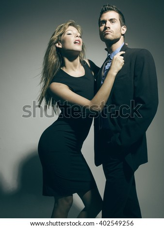 elegant fashionable couple in black suit and dress