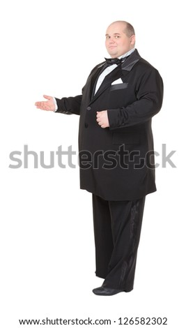 Elegant fat man in a dinner jacket and bow tie smiling charmingly as he holds out his hand to the side gesturing in that direction - stock photo