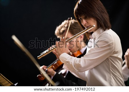 Elegant female flutist performing on stage with orchestra. - stock photo