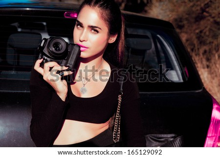 Elegant female photographer holding a digital camera. Outdoors horizontal shot . Attractive woman. Tanned woman with make up - stock photo