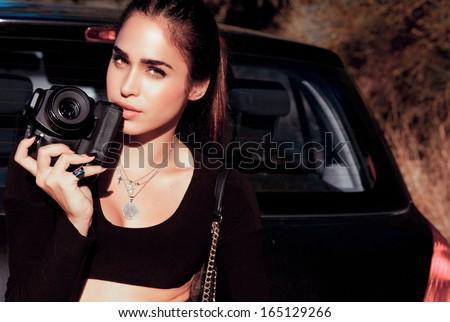 Elegant female photographer holding a digital camera. Outdoors horizontal shot . Attractive woman by a car. Urban fashion.  - stock photo