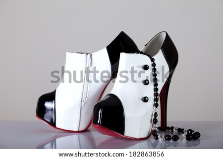 Elegant female shoes with black necklace, shot with natural soft shadow and reflection
