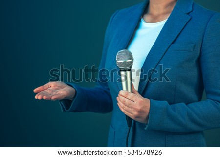 Elegant female television journalist doing business reportage, holding microphone in hands, breaking news concept