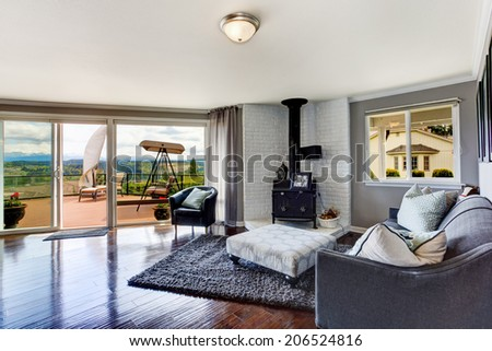 Elegant furnished corner in luxury house living room. View of antique stove with white brick background, coach and chair. - stock photo